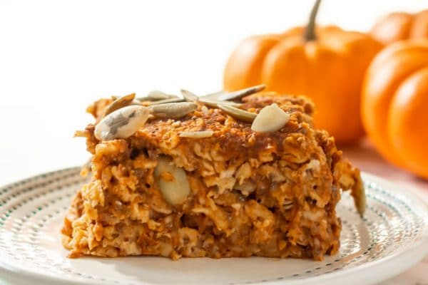 a sliced of baked pumpkin oatmeal with pumpkin seeds on top and mini pumpkins in the background