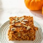 A square of baked pumpkin oatmeal topped with pepitas on a small ivory plate with tiny teal dots on the border.