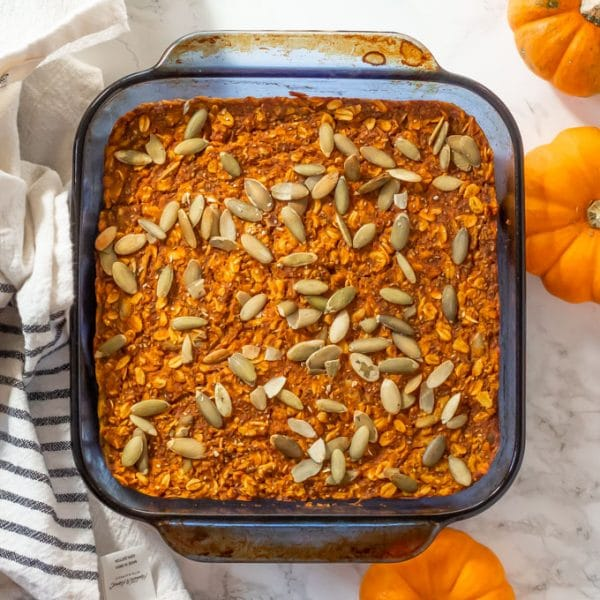 pumpkin baked oatmeal topped with pepitas in a blue square glass pyrex pan