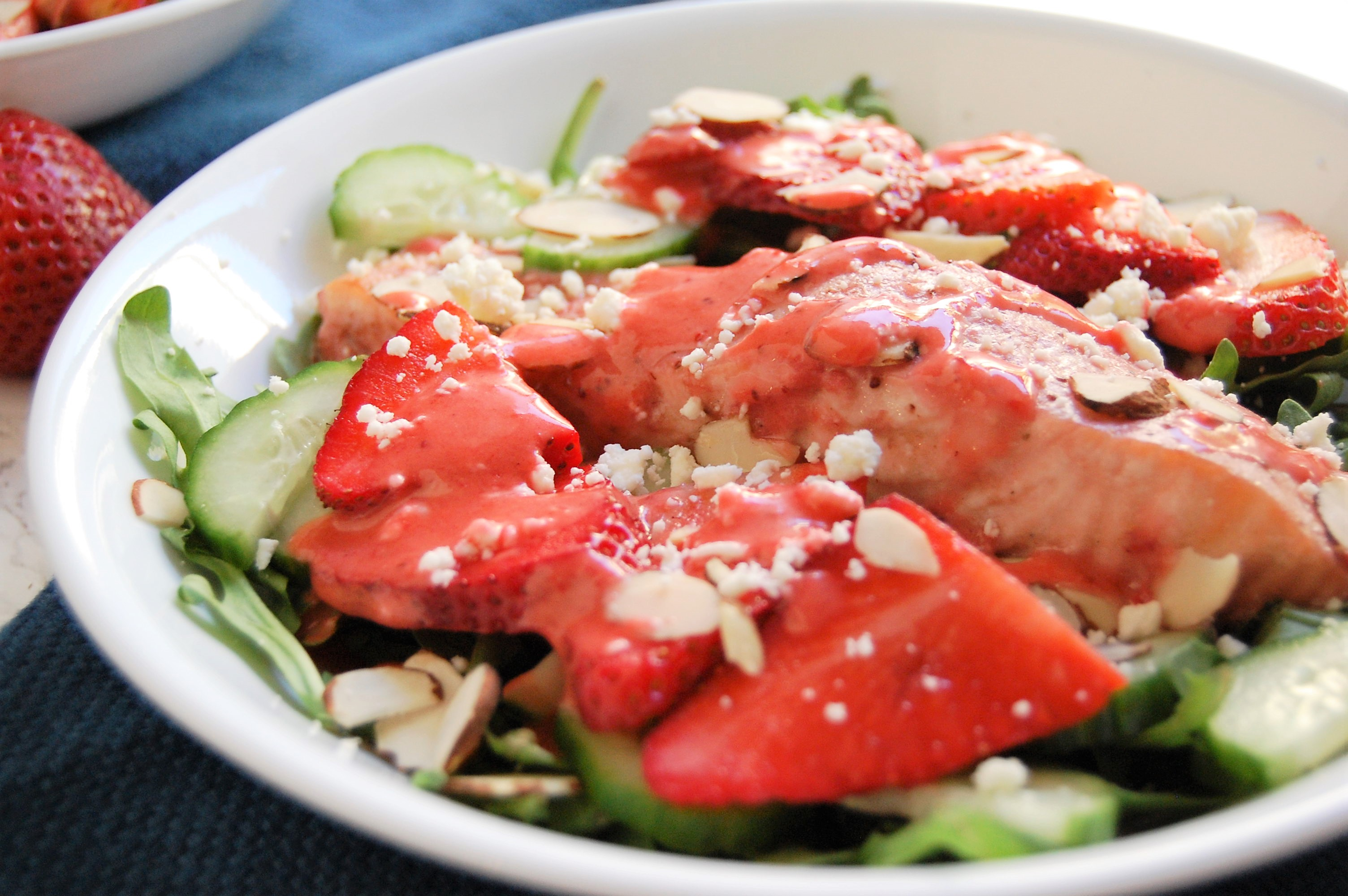 This fresh, springtime salad is a healthy entree salad with salmon baked in strawberry dressing. It has crisp cucumber toppings, sweet strawberries, crunchy almonds, creamy feta, and all served over a bed of spicy arugula. Try this easy, 30 minute dinner! | healthy recipe, salad recipe, salmon salad, strawberry salad, 30 minute meal, 30 minute dinner, pretty food, strawberries, strawberry salmon salad, dietitian recipe, nutritious recipe, healthy recipe |