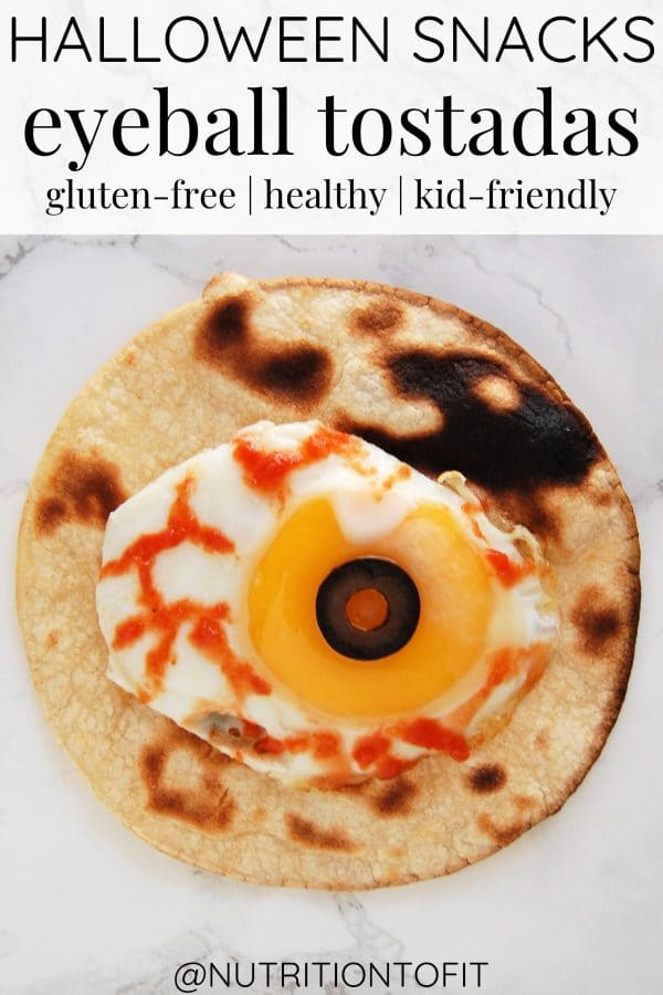 A healthy Halloween snack of a spooky eyeball tostada, with a fried egg, a black olive eye over the yolk, and hot sauce bloody veins in the eye.