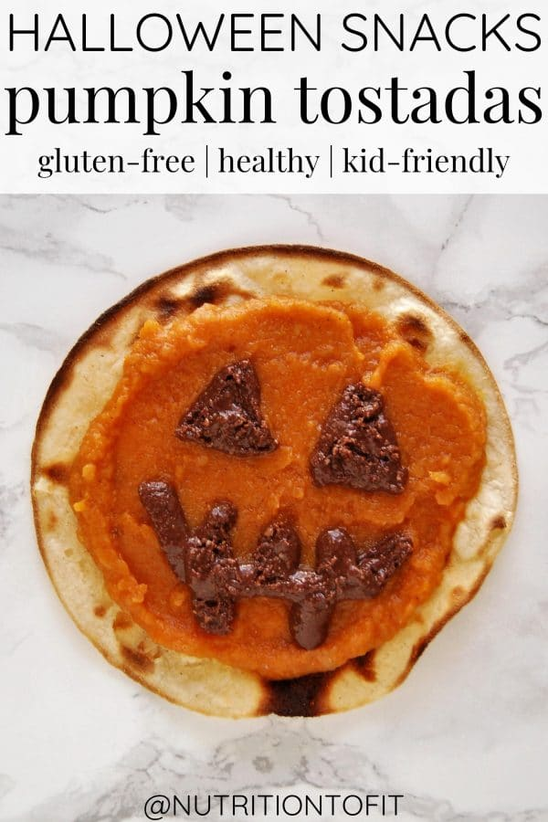 A healthy Halloween snack of a pumpkin tostada with pumpkin spread on a tostada and a jack'o'lantern face made from chocolate sunflower seed butter.