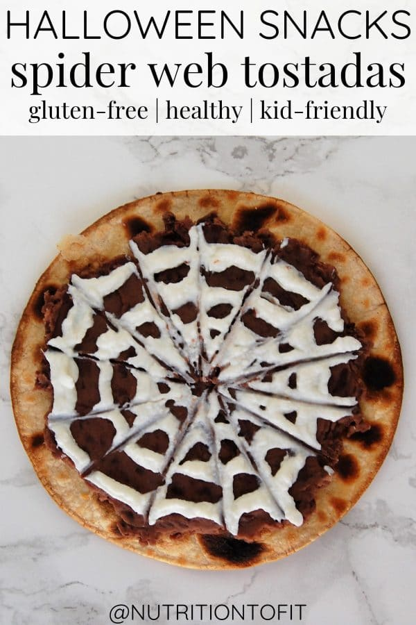 A healthy Halloween spooky tostada with mashed black beans and a greek yogurt spider web.