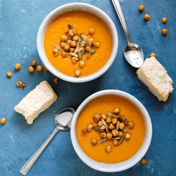 Square image of two bowls of spiced sweet potato carrot soup on a blue background with rectangular biscuits.