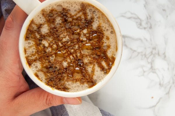 A warm ivory mug with a cozy gingerbread chai latte with molasses drizzle on top being held in a left hand.