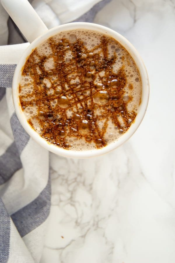 A warm ivory mug with a cozy gingerbread chai latte with molasses drizzle on top.