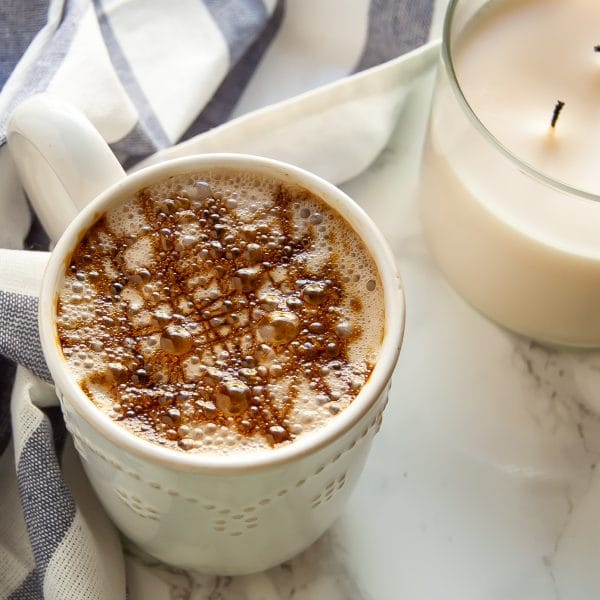 A warm ivory mug with a cozy gingerbread chai latte with molasses drizzle on top next to a candle.