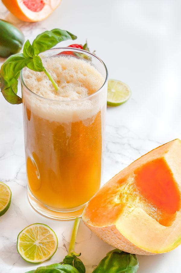 Tall glass of cantaloupe basil agua fresca next to a slice of cantaloupe.
