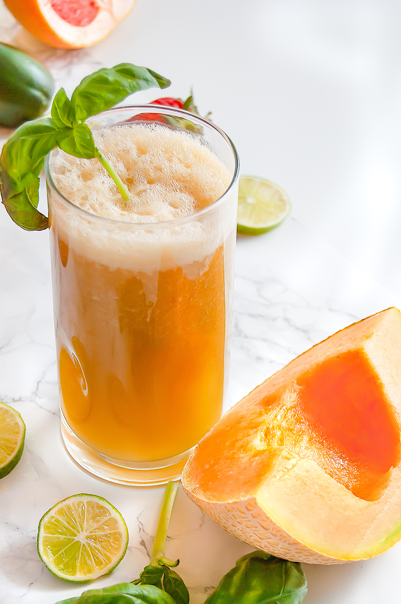 Tall glass of cantaloupe basil agua fresca next to a slice of cantaloupe.