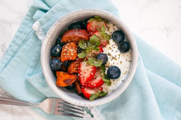 Sweet potato bowl with fresh berries, Greek yogurt, and seeds.