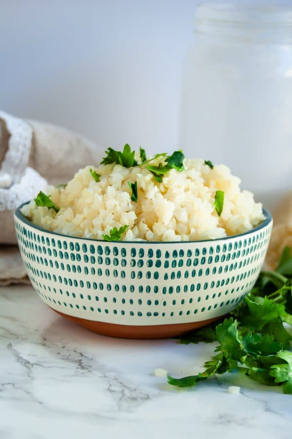 Coconut cauliflower rice is a simple, delicious side that will become a versatile, healthy dinner recipe staple! | #glutenfree #dairyfree #healthydinnerrecipe #cauliflowerrice #vegan #healthyrecipe | nutritiontofit.com