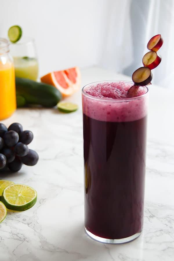 tall glass of vibrant dark purple grape agua fresca