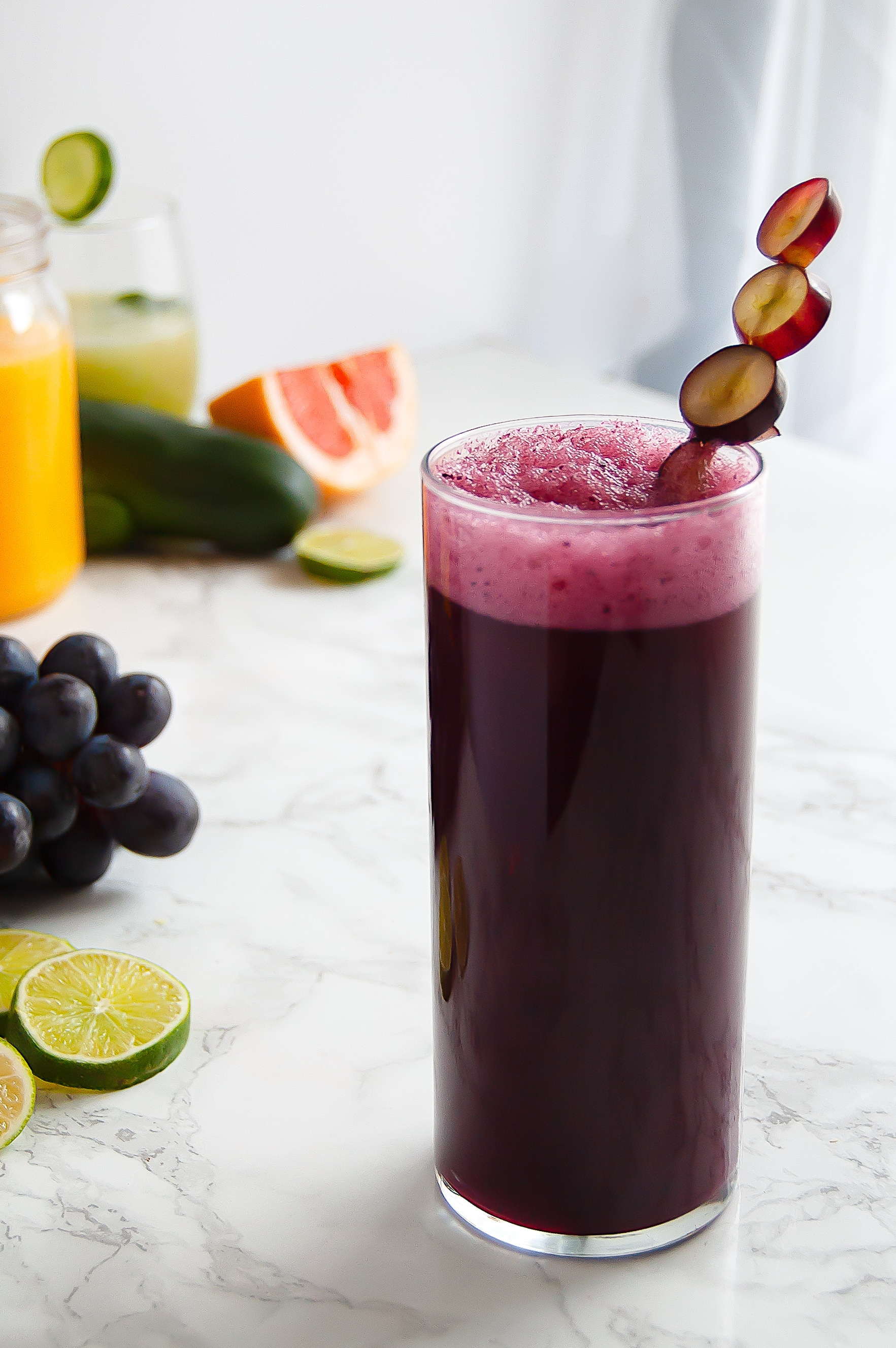 tall glass of vibrant dark purple grape agua fresca