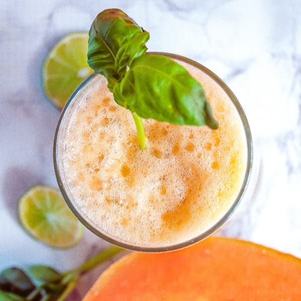 Overhead picture of a glass of cantaloupe basil agua fresca with a pretty soft orange froth and basil garnish.