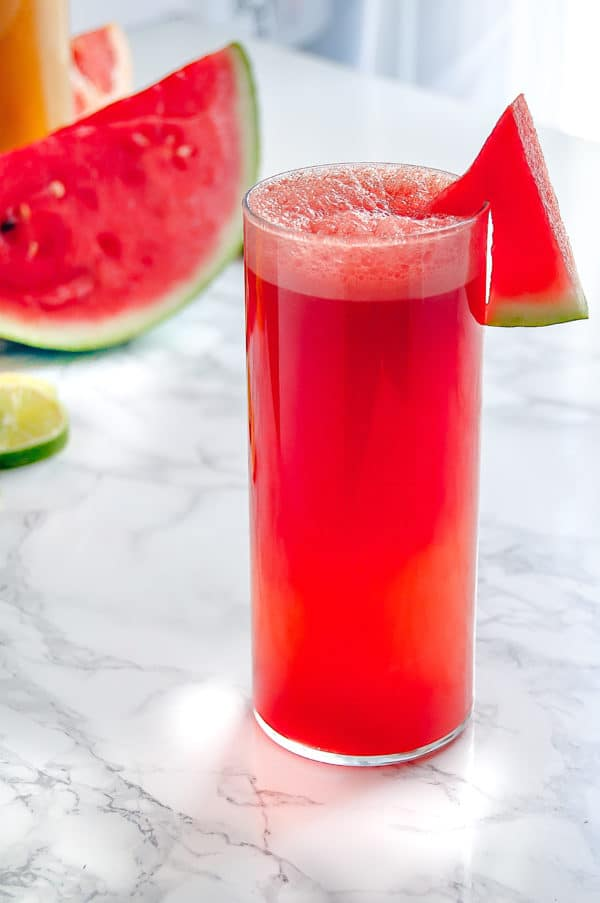 Tall glass of watermelon agua fresca with watermelon and limes in the background.