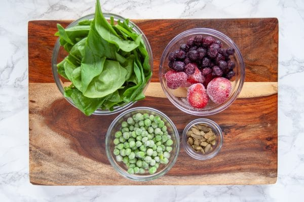 Ingredients for a blueberry strawberry sweet pea green smoothie. Check off five servings of fruits and vegetables in your day by following the NTF 5-a-Day Green Smoothie guide! Completely customizable.