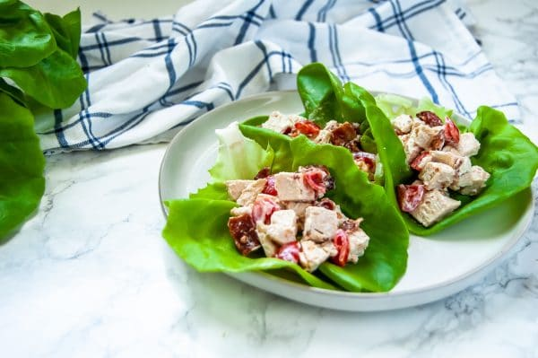 A horizontal image with a plate with turkey lettuce BLT cups on it - there are three leaves of butter lettuce with a creamy turkey, bacon, tomato salad inside of them.