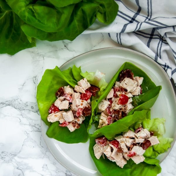 A square image of a plate with turkey lettuce BLT cups on it - there are three leaves of butter lettuce with a creamy turkey, bacon, tomato salad inside of them.