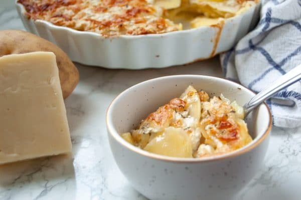Thinly sliced yukon gold potatoes baked with a greek yogurt-based cream sauce & cheese for a lighter scalloped potato gratin. A healthy holiday side dish!