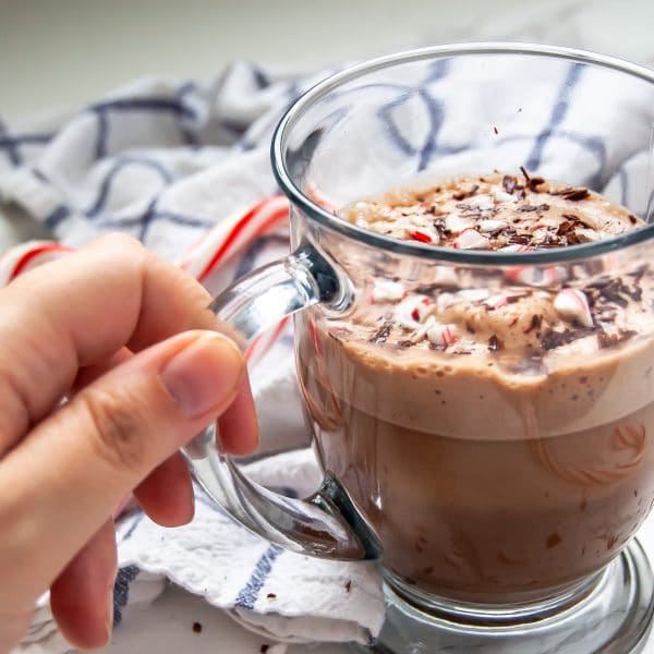 A hand holding a glass mug of peppermint hot chocolate.