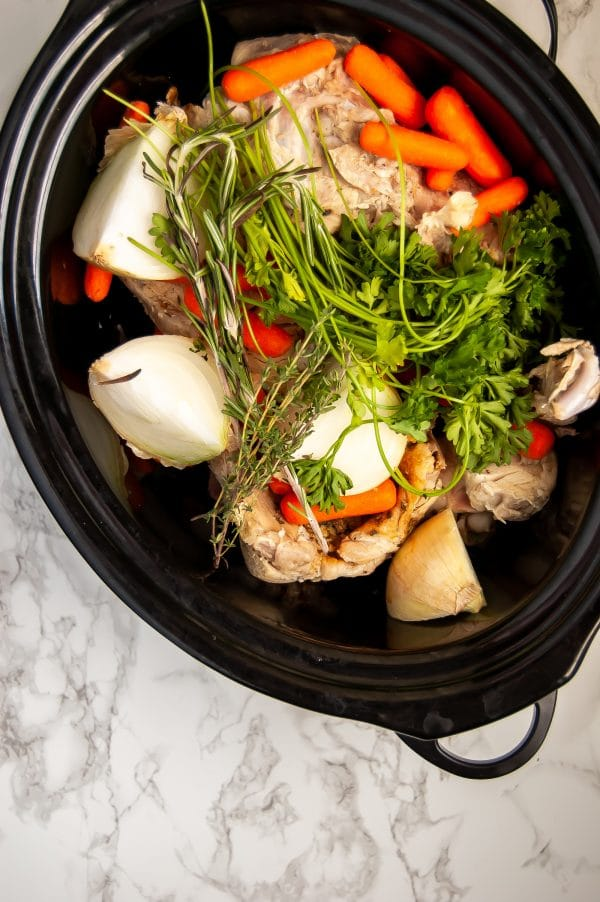 A slow cooker filled with the fresh ingredients for the easiest slow cooker turkey stock recipe.