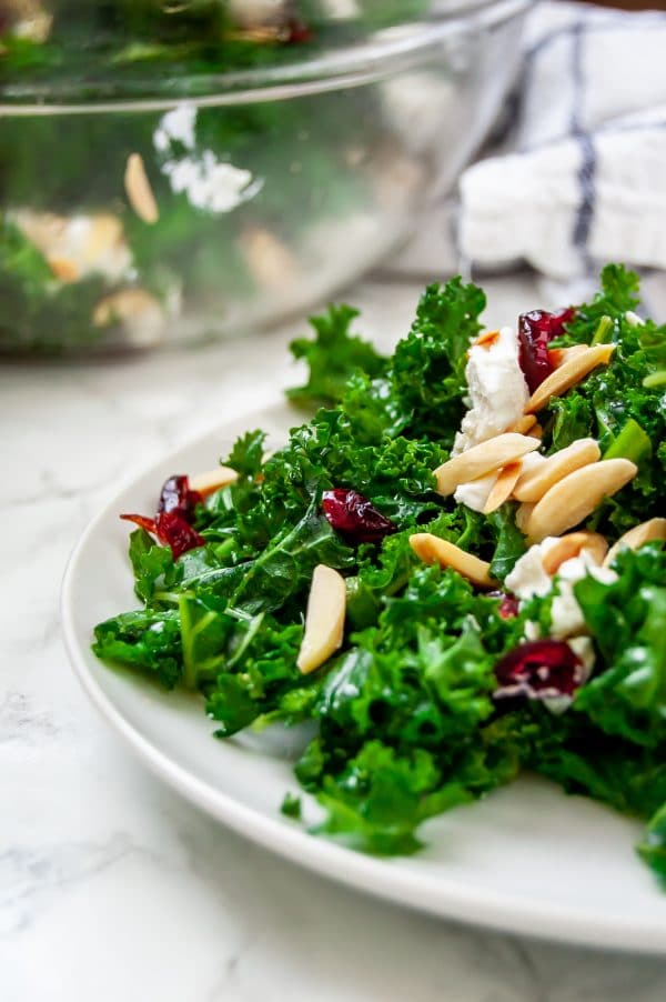 A close up shot of winter kale salad with cranberries, goat cheese, and toasted almonds on a white plate.