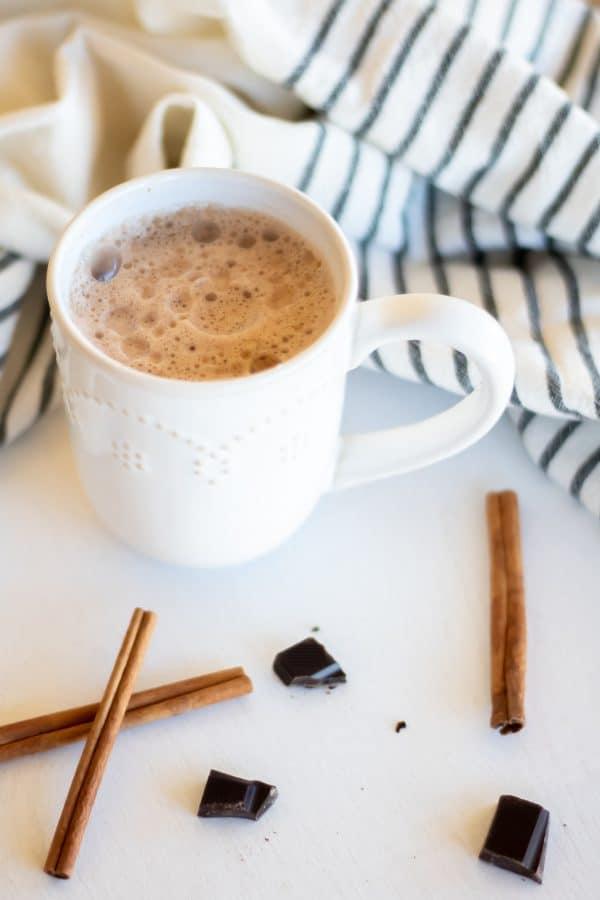A white mug of chocolate chai tea with cinnamon sticks and dark chocolate on a white board.