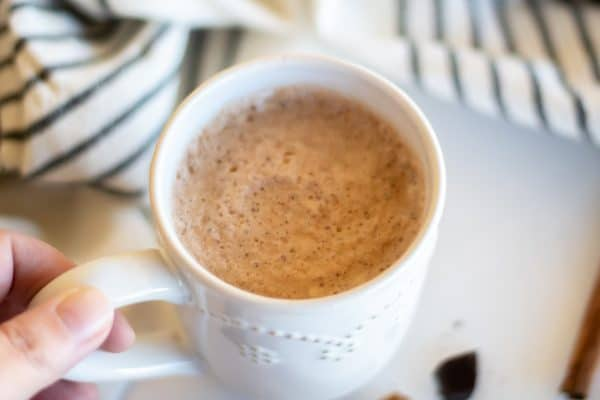 A hand holding a cozy white mug of chocolate chai tea.