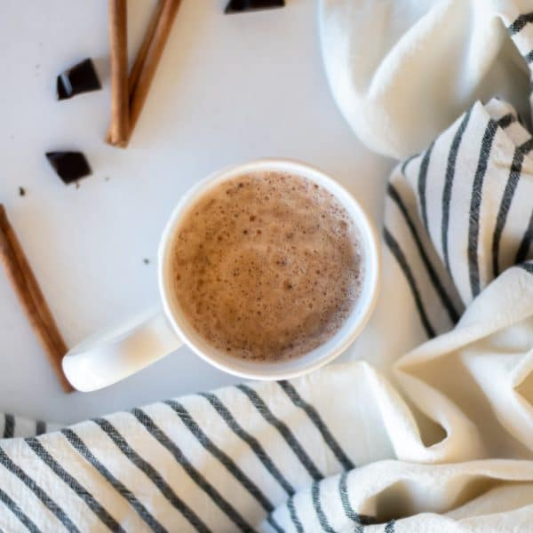 An overhead shot looking down at a mug of chocolate chai tea that is foamy and swirly on top.