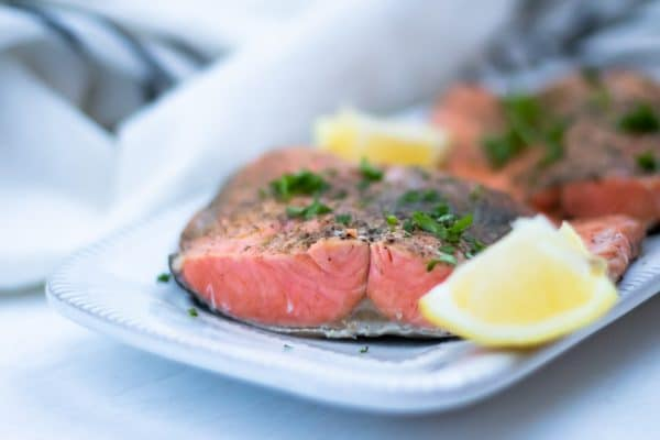 Close up of beautifully cooked salmon fillets with lemon wedges and fresh parsley on a white platter.