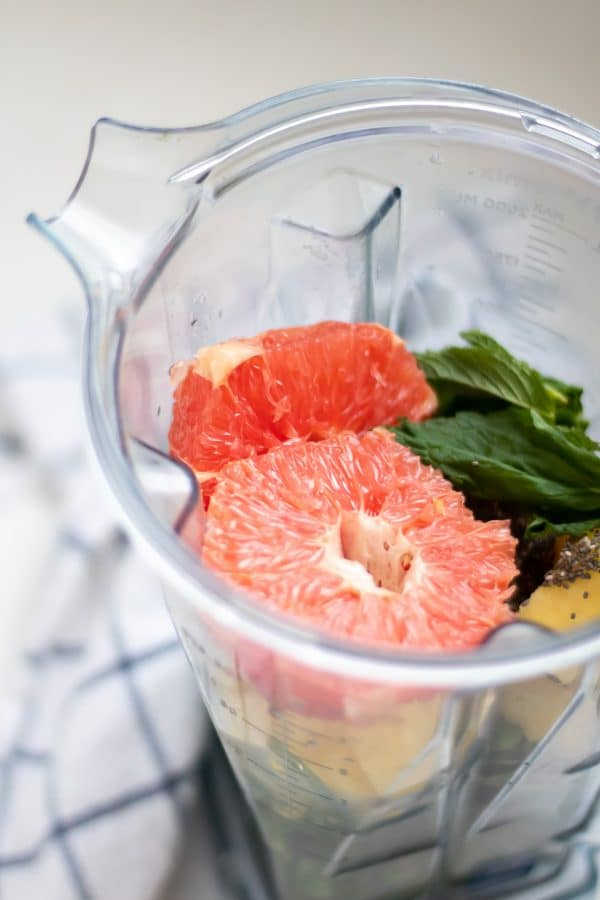 A vitamix blender full of grapefruit smoothie ingredients.