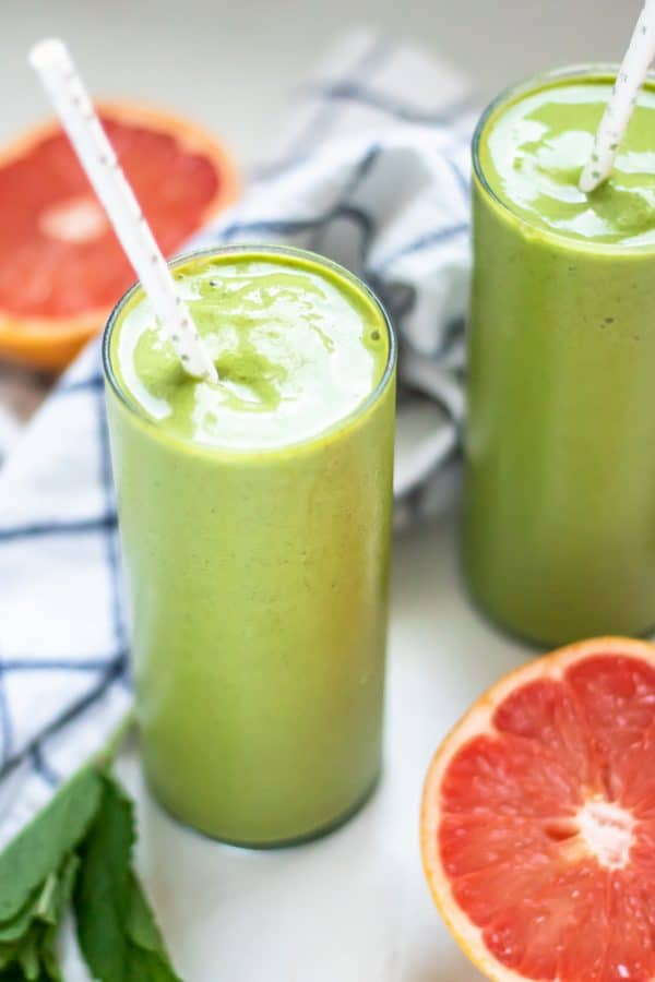 Tall thin glasses of green grapefruit smoothies with pink grapefruits and fresh mint on the side.