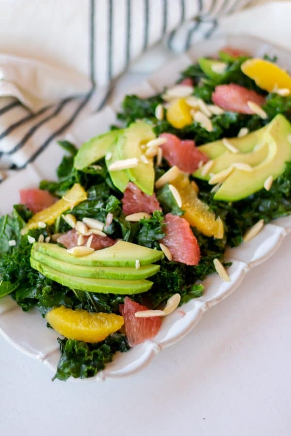 Rectangular plate full of a citrus kale salad massaged with grapefruit vinaigrette and topped with sliced avocado, citrus segments, and slivered almonds.