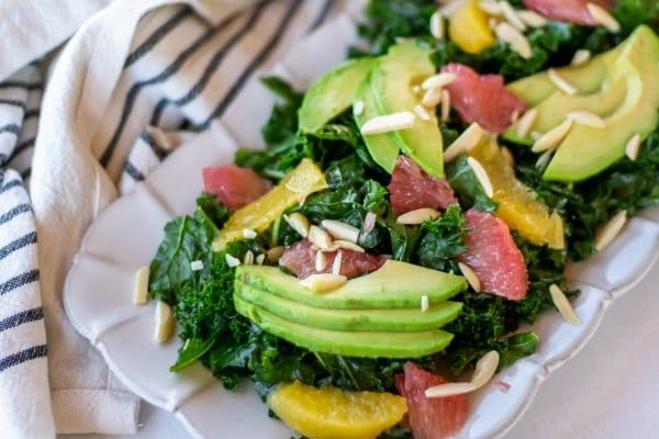 Close up of a citrus kale salad massaged with grapefruit vinaigrette and topped with sliced avocado, citrus segments, and slivered almonds.