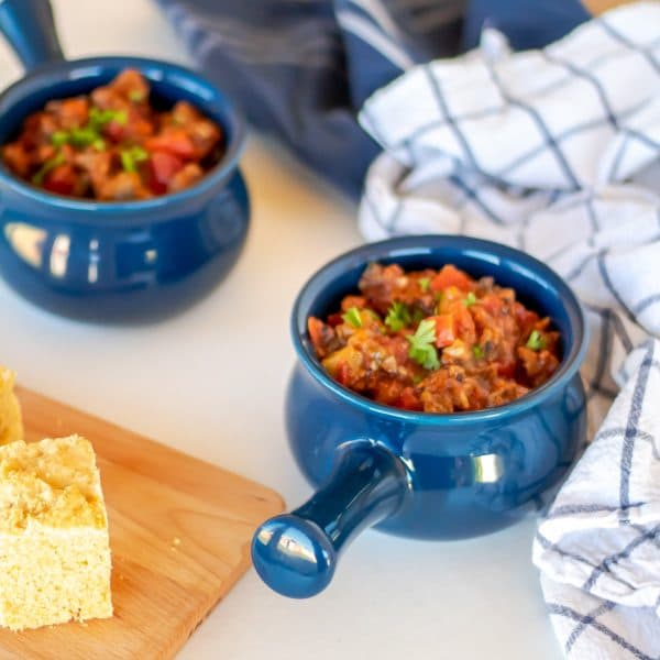 Two blue crocks of beanless chili with beef and vegetables.