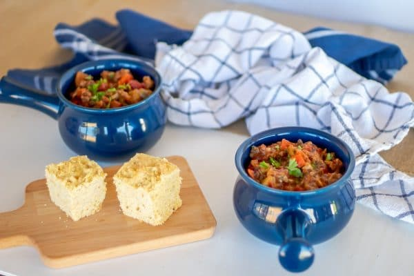 Blue crocks of beanless chili with beef and vegetables served with cornbread on the side.