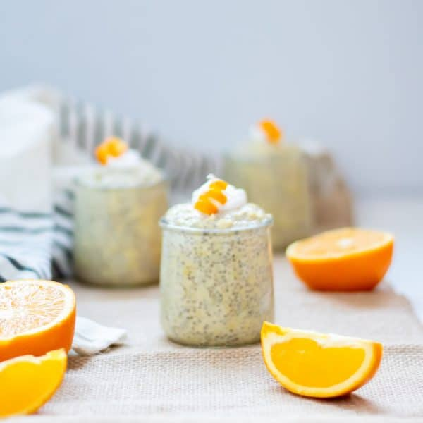 3 small glasses of orange chia pudding with collagen on a burlap table runner with orange slices. Garnished with coconut whipped cream and curled orange peel garnishes.