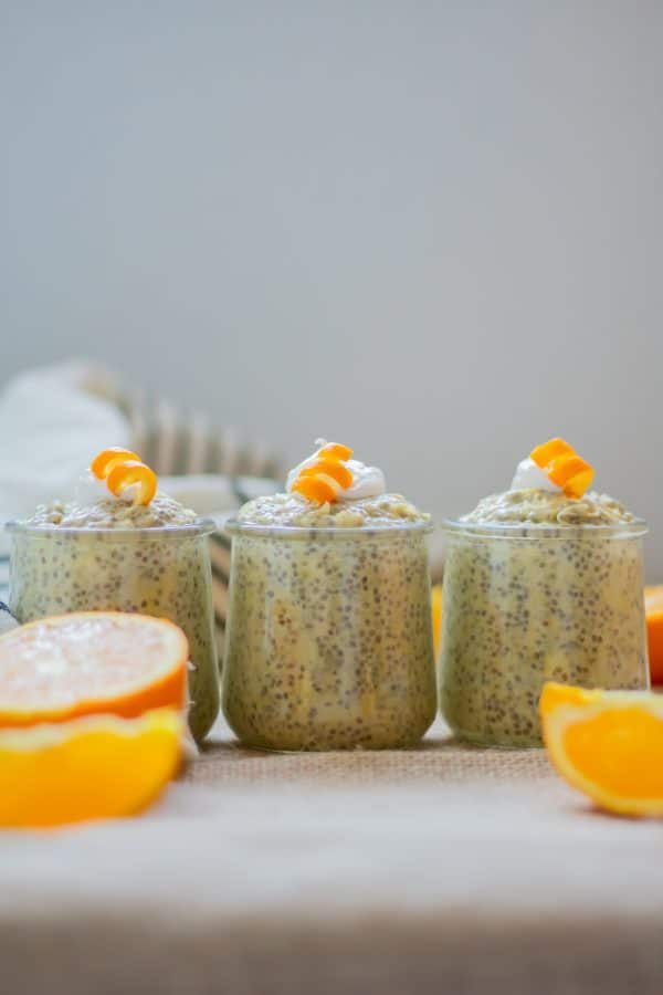 3 small glass jars of orange chia pudding with collagen lined up next to each other topped with coconut whipped cream and orange curls.