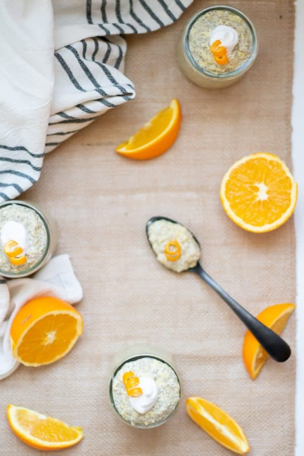 Glass cups of orange chia pudding with a black spoon with a spoonful of chia pudding, accented by orange slices all on a burlap runner.