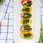 White rectangular serving platter with brie and pesto stuffed mini bell peppers on a blue checked white towel.