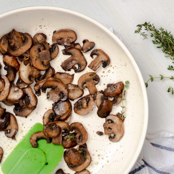 healthy, easy sauteed mushrooms in a ceramic nonstick skillet with a green spatula and garnished with fresh thyme.