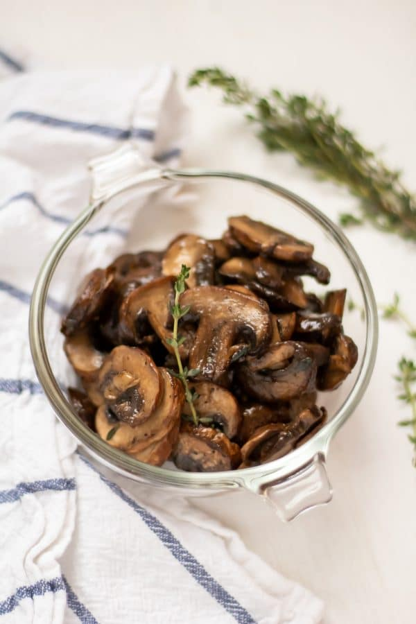 Overhead shot of healthy, easy sauteed mushrooms in a glass bowl garnished with a sprig of thyme.