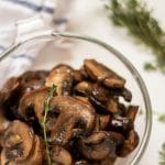 healthy, easy sauteed mushrooms in a glass bowl garnished with a sprig of thyme.
