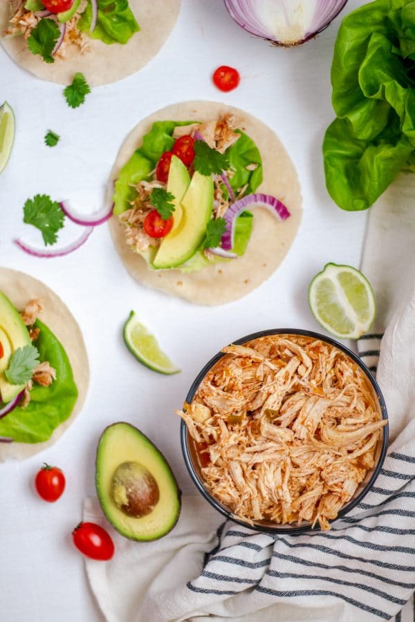 A glass bowl of instant pot salsa chicken flanked by tacos and taco toppings.