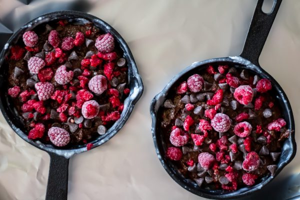 Two six inch skillets filled with brownie batter and topped with frozen raspberries and chocolate chips.