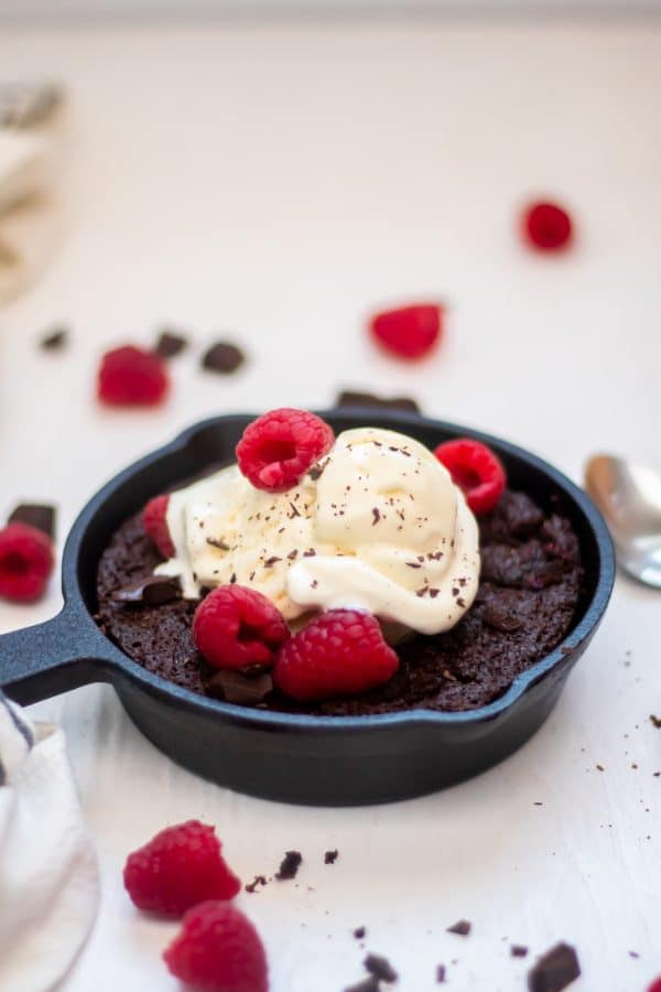 Skillet brownies with raspberries in a six inch skillet topped with vanilla bean ice cream and fresh raspberries.