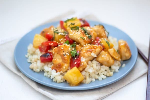 A blue plate full of cauliflower rice topped with healthy sweet and sour chicken and garnished with fresh herbs.