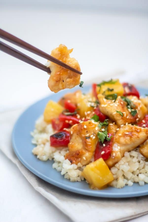 Chopsticks holding up a piece of chicken from a blue plate of healthy sweet and sour chicken.