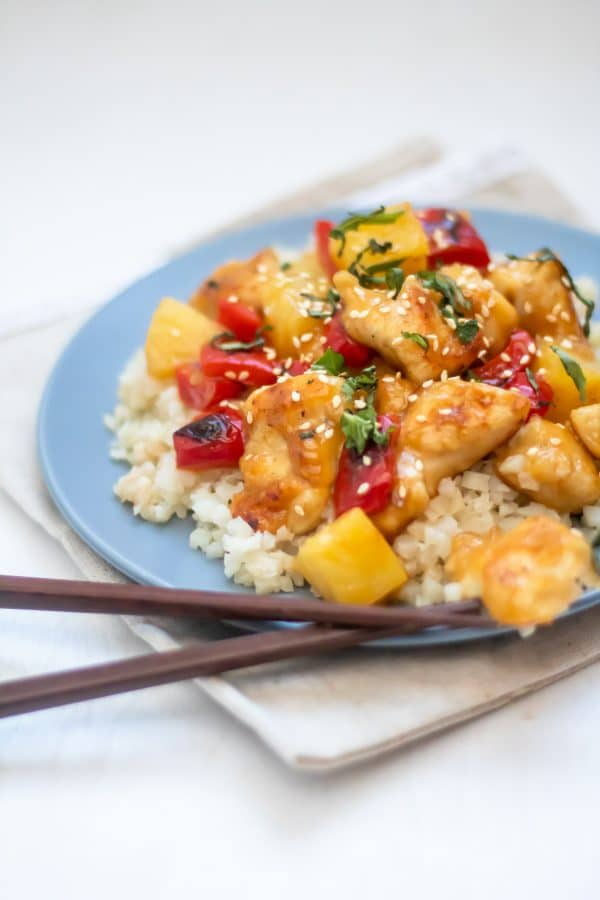 A blue plate full of cauliflower rice topped with healthy sweet and sour chicken and garnished with fresh herbs. It's sitting on a light brown linen napkin with brown chopsticks by the plate.