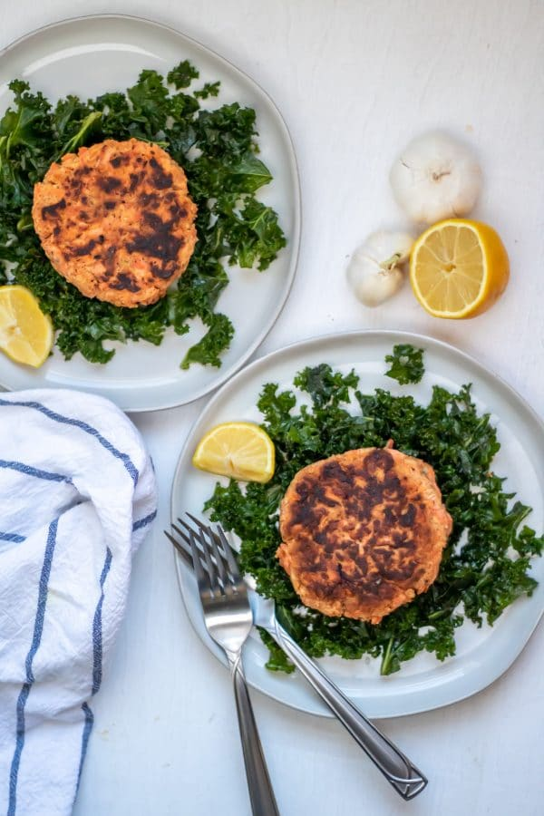 Two salmon patties on plates of massaged kale salad with garlic and lemon on the side.
